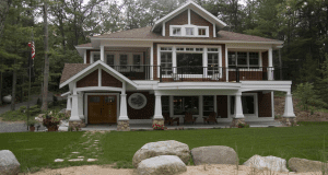 A brown two-story house with a green lawn.